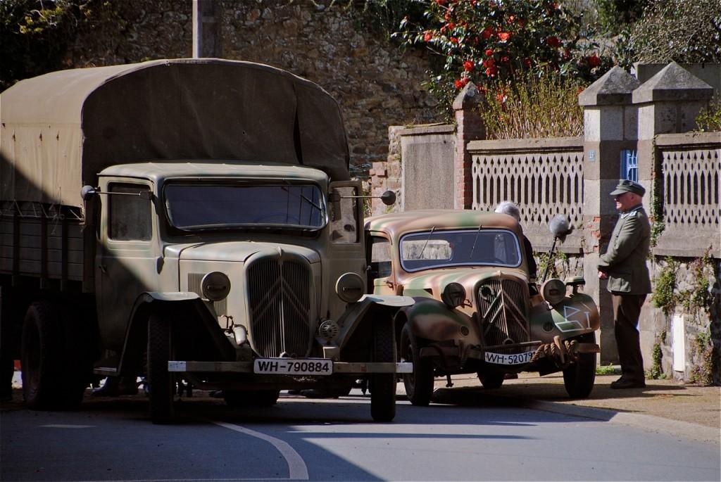 Installation des véhicules dans la rue : deux Citroën, un camion U23 et une Traction, toutes les deux en livrée militaire.