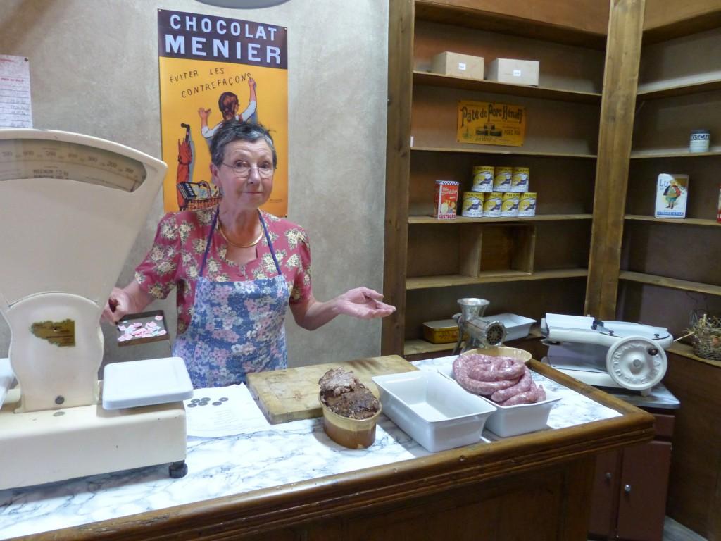 Dans le décor de la boutique, la vendeuse est bien réelle, ainsi que le pâté et les saucisses !